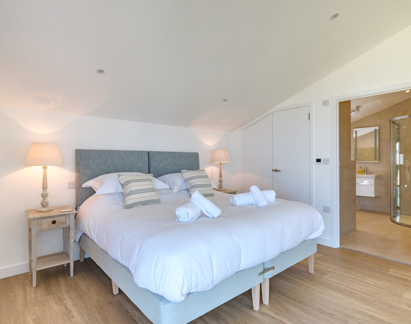 Beautifully styled and furnished master bedroom with a super king size bed, which can be made into two twin beds and a bathroom ensuite at Point Break, a self catering, holiday house in Polzeath.