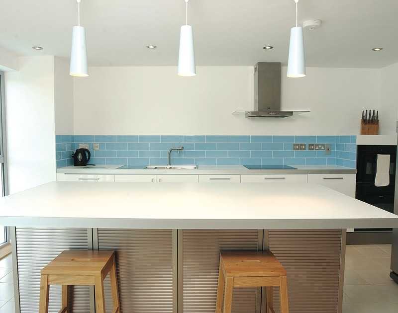 The stylish contemporary kitchen at Rock Pipit, a holiday house at Polzeath, Cornwall, with its large central work top.