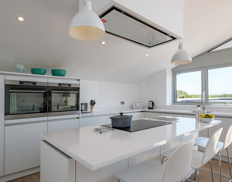 Spotless, bright, white, modern kitchen at Point Break, a self catering, holiday house in Polzeath, North Cornwall.