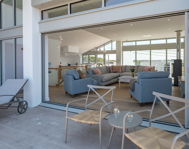 The sitting room and exterior balcony merge into one by opening fully the bi-folding doors at luxury holiday house Point Break in Polzeath.