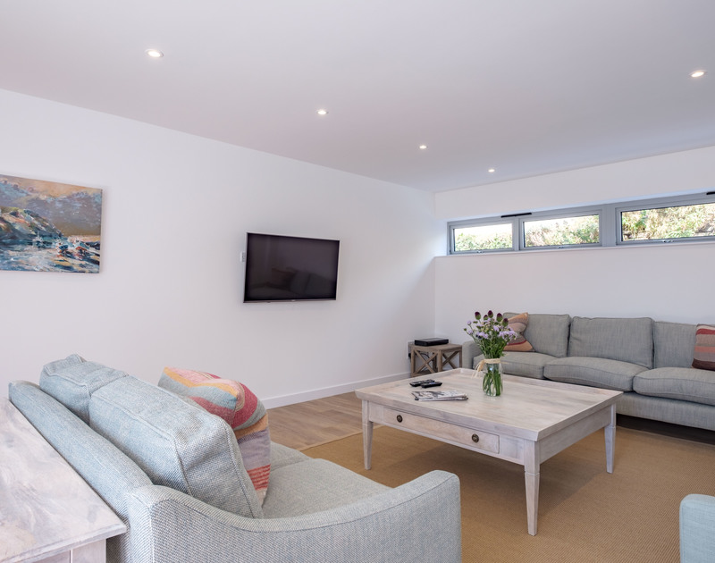Relax after a day in the surf on the comfortable seating in the TV room at Point Break, a luxury holiday house to rent in Polzeath.