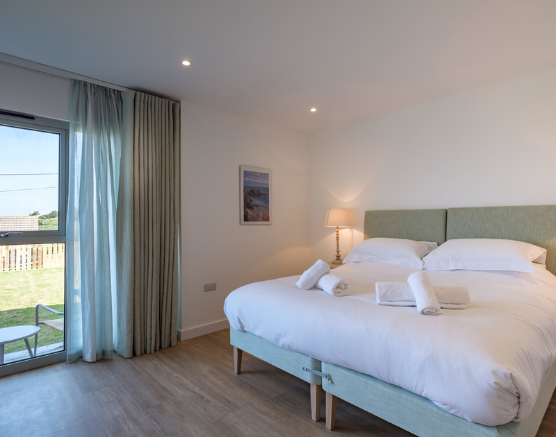 The elegant ground floor bedroom with a super king sized bed at self catering, holiday property Point Break in Polzeath.