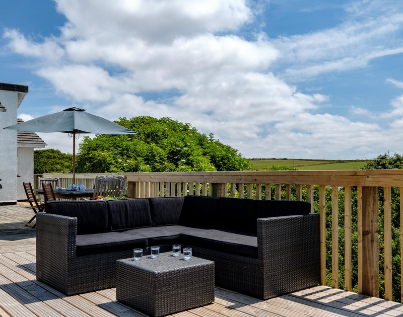Plenty of garden furniture on the decking for lazy summer days at holiday rental Quarry Cottage in Polzeath, Cornwall.