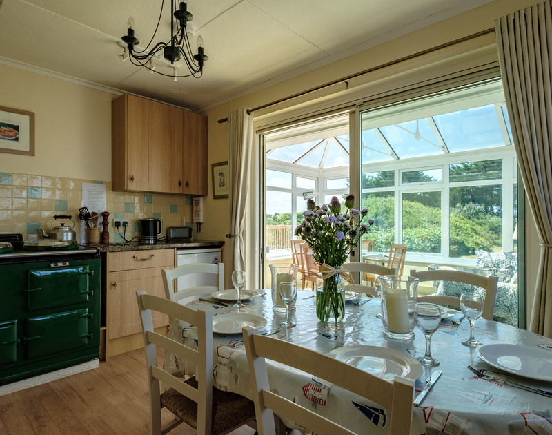 The dining table in the kitchen at Quarry Cottage, a coastal holiday house to rent in Polzeath.