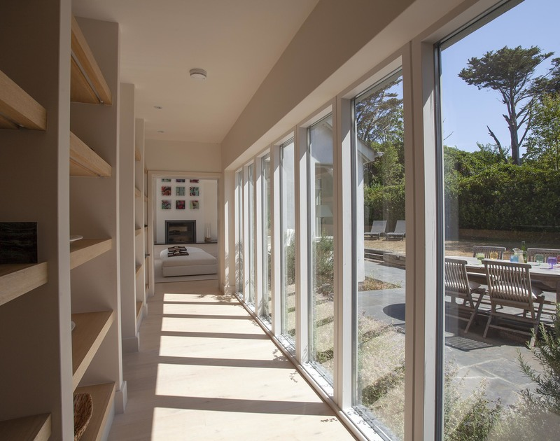 Useful shelving and full length glass windows line the elegant hallway that looks out onto the gardens at Church lane House in Daymer Bay.