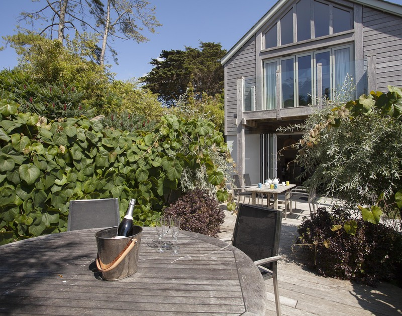 Have a glass of fizz at the garden table and admire the glass and wood clad exterior of self catering, holiday home Church Lane House in Daymer Bay.