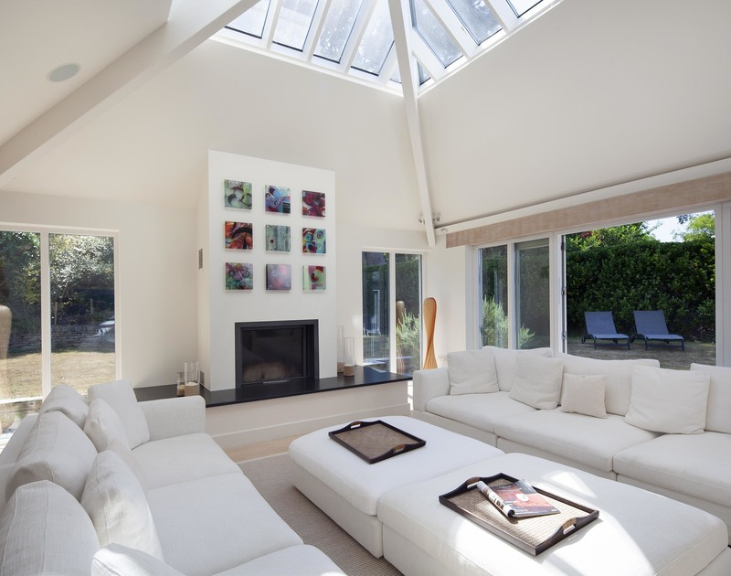 Natural light fills the elegant living room at Church Lane House from the glazed walls and vaulted ceiling with glass, there's also a modern woodburner and sumptuous sofas to relax on.