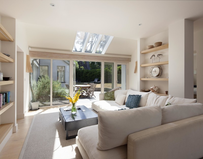 Serene neutral tones and a vast corner sofa with glass french doors at Church Lane House.