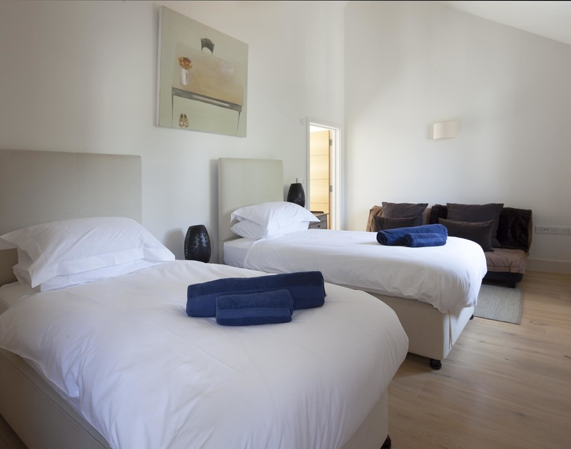 Elegant twin bedroom with a sofa, one of three twin bedded rooms at Church Lane House in Daymer Bay, Cornwall.