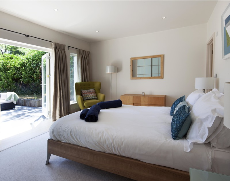 Luxurious ground floor, king size bedroom with a bathroom ensuite and access out to the garden through large glass doors at self catering holiday property Church Lane House in Daymer Bay.