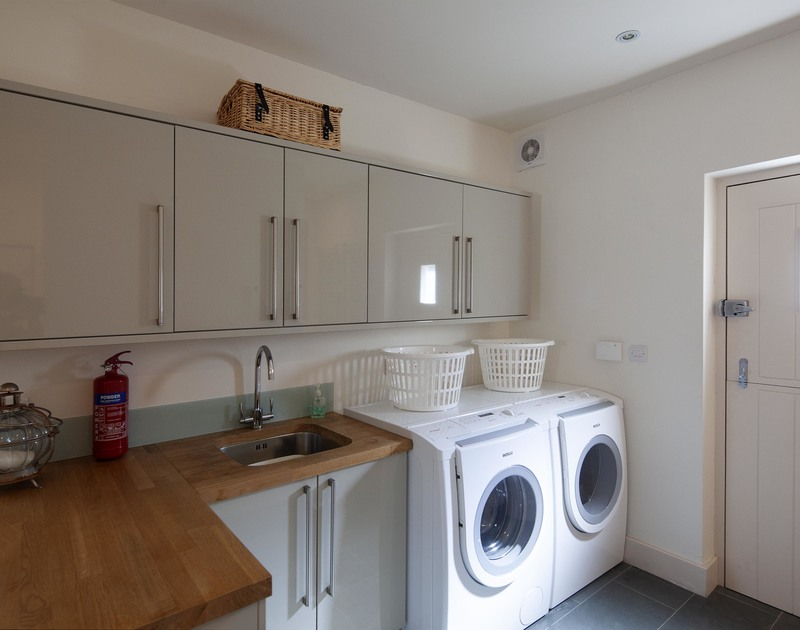 Well designed and equipped utility room at luxury holiday house Church Lane House just off Daymer Lane, in walking distance of the beach.