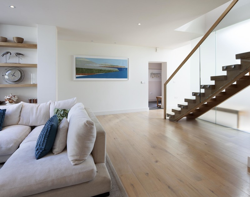 Polished wooden floorboards and a contemporary glass and wood staircase in luxury, self catering, holiday property Church Lane House.