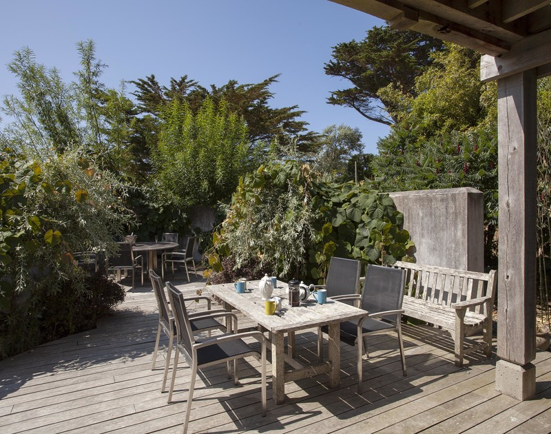 Wonderful mature plants surround the peaceful wooden, decked terrace outside at self catering Church Lane House in Daymer Bay.