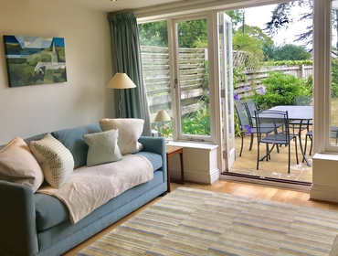 The sitting room at holiday rental Lowenna Manor 9, with light from the glass windows and french doors out to the pretty garden in Rock, Cornwall