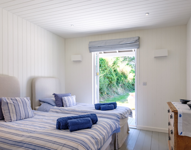 The bright twin bedroom in the Pool House at Trerokken, with patio doors out into the garden and into the wet room shower room.