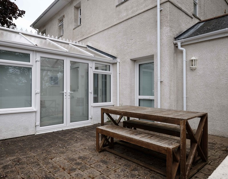 An external view of self catering, holiday apartment St Martins showing the patio area and the conservatory.
