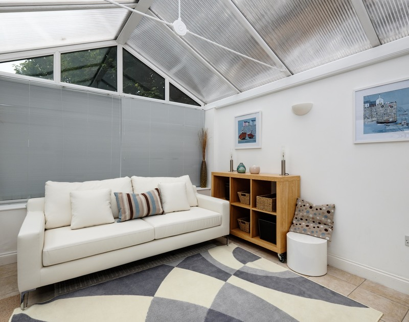 The light conservatory with a comfortable sofa in St Martins, a self catering holiday apartment in Lundy House on the Rock Road in Cornwall.