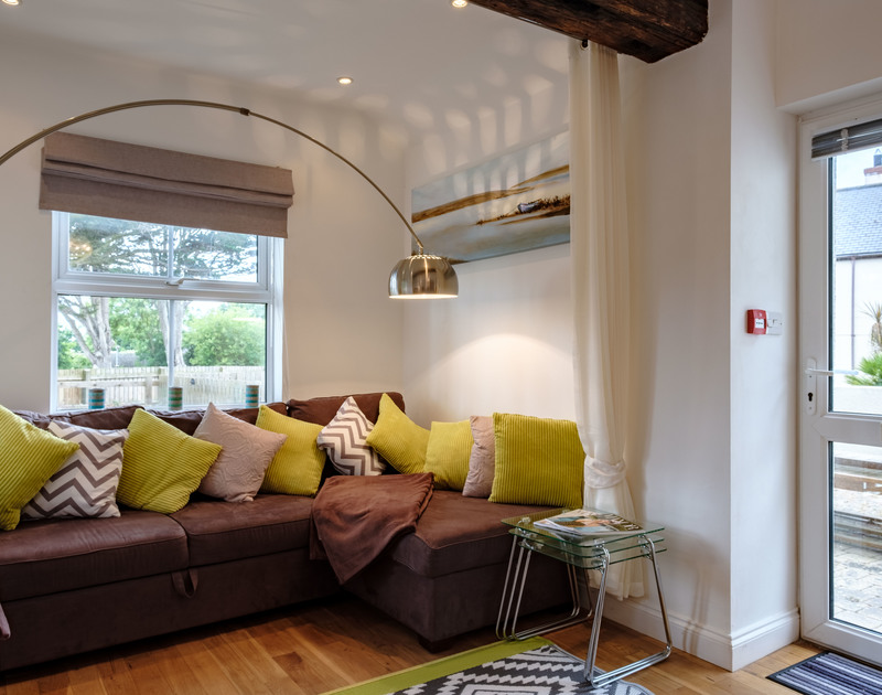 The corner sofa in open plan holiday apartment St Martins with an external glass door.