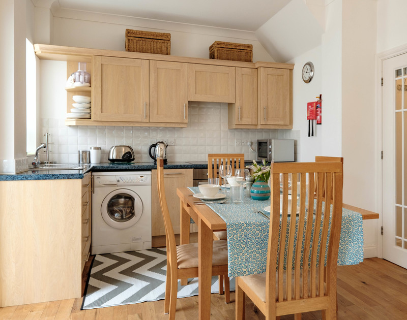 The well equipped kitchen and dining table at self catering holiday apartment St Martins in Rock, North Cornwall.
