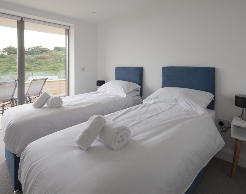 One of the flexible zip and link bedrooms at Slatewater with access onto the ground floor decked balcony, a luxury self catering holiday house to rent in Polzeath, Cornwall.