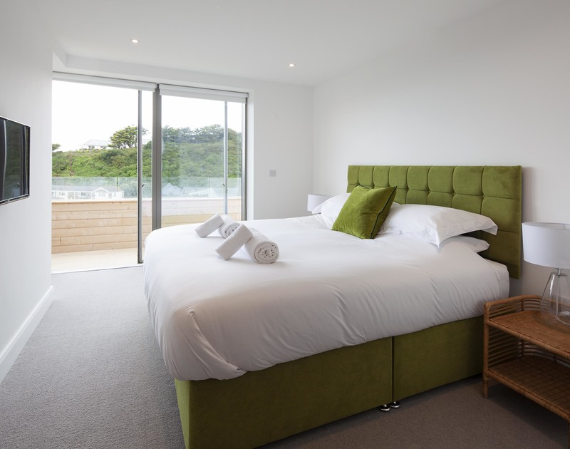 Stylish upholstered master bed in the master bedroom at Slatewater with patio doors out to the ground floor balcony.