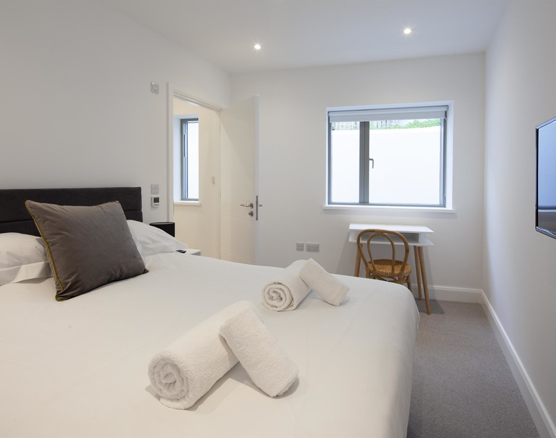 A king size bedroom with an ensuite shower room at luxury self catering holiday property Slatewater in Polzeath, North Cornwall.