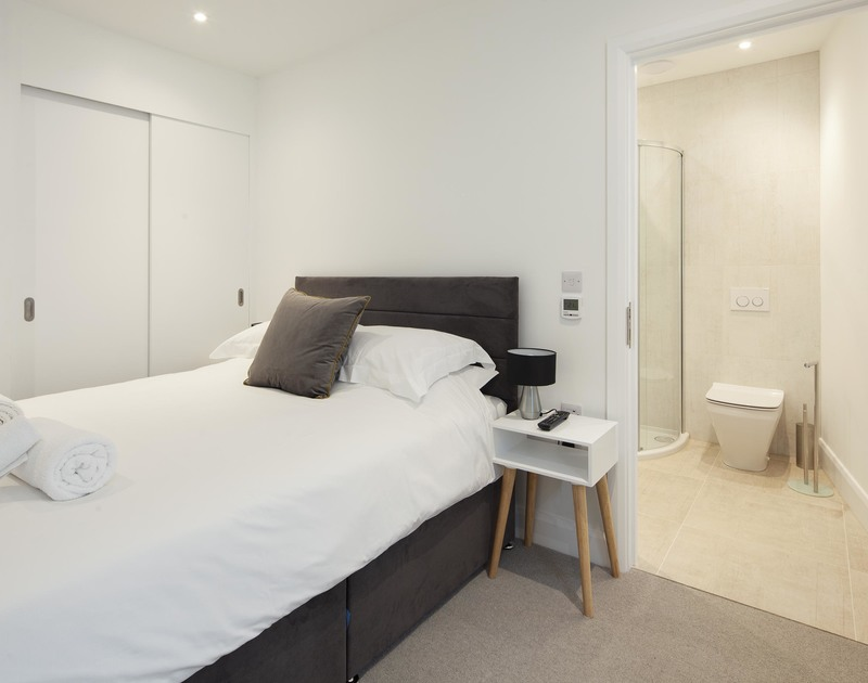 The  cosy king size bedroom with a grey upholstered bed, plenty of cupboard space and a shower room ensuite at Slatewater, a luxury holiday house to rent in Polzeath in North Cornwall.