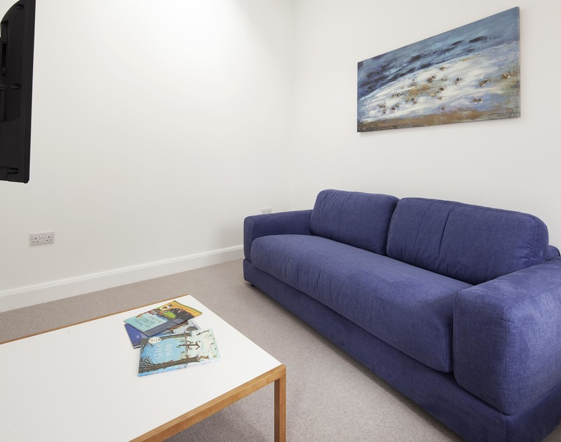 A comfy sofa in the separate TV room in Slatewater, a luxury holiday rental in Polzeath on the North Cornwall, Coast.