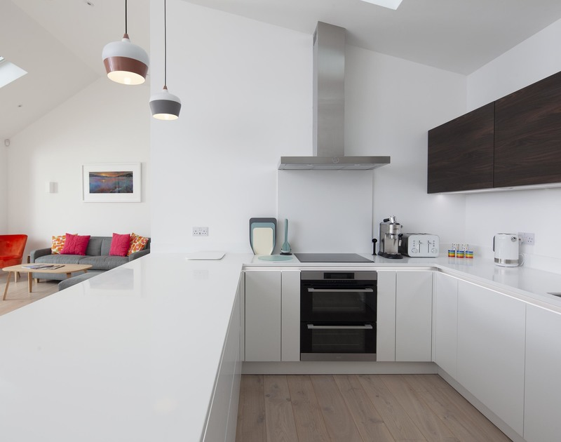 Immaculate, white, fitted kitchen area on the open plan ground floor at Slatewater, in Polzeath, Cornwall.