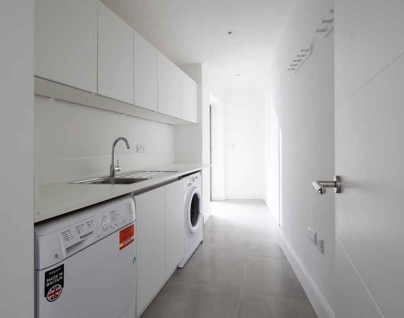 The useful utility room with hooks for coats, wetsuits etc and access to the outside shower and tap at Slatewater, a luxury, self catering holiday rental in Polzeath.