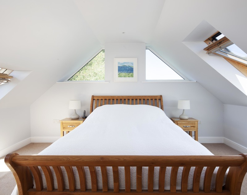 One of two king size bedrooms on the first floor at Saltrock with skylights and feature windows.