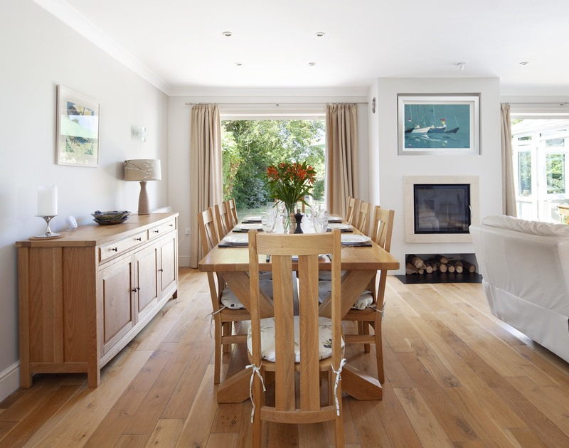 Elegant dining table with large glass patio doors out to the garden at Saltrock near the Camel Estuary in Cornwall.