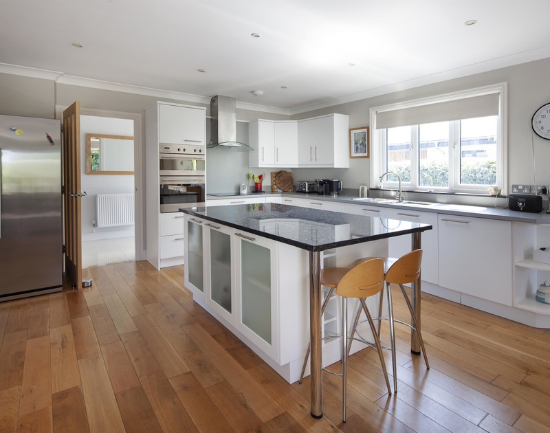 Modern, sleek kitchen of Saltrock, a holiday house in Rock, Cornwall, with its central island worktop.