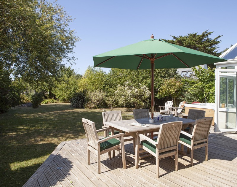 Well established plants in the good sized, lawned garden at Saltrock with outdoor furniture for alfresco meals.