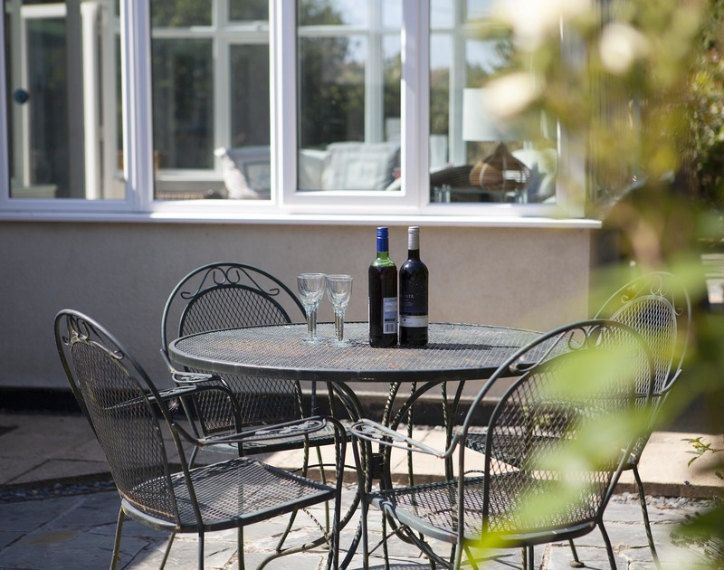 Enjoy a sundowner on the slate paved terrace outside at self catering, holiday house Saltrock.in Rock, Cornwall.