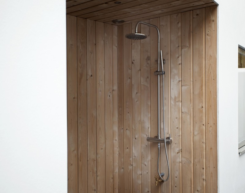 Wood lined shower enclosure outside at Slatewater, a luxury holiday house to rent in Polzeath on the North Cornish Coast.