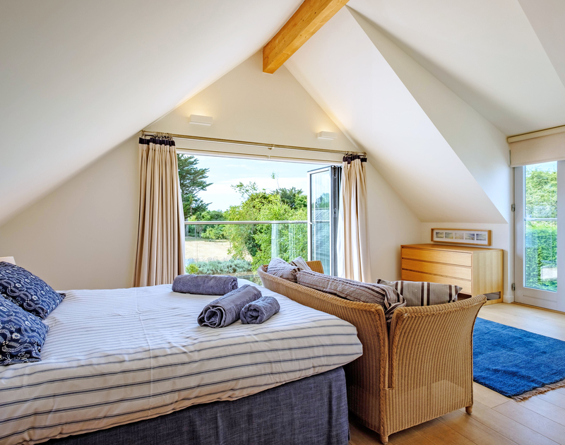 Beautifully furnished with a coastal coloured theme in the king size bedroom that has folding doors onto a balcony overlooking the garden at Trerokken in Rock.
