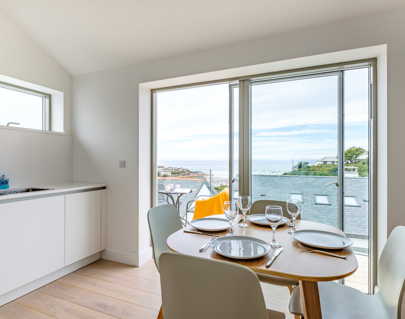 The dining area with a sea view at Backwater, a luxury holiday rental in Polzeath, Cornwall.