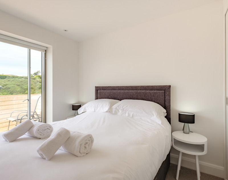 The luxurious master bedroom at Backwater with access out onto the wooden terrace, in walking distance of the beach, surf and shops of Polzeath in North Cornwall.