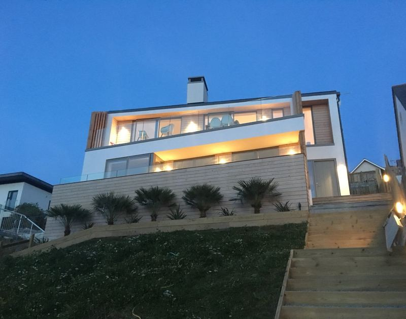 Stunning exterior of Slatewater, lit up by night in Polzeath, North Cornwall.