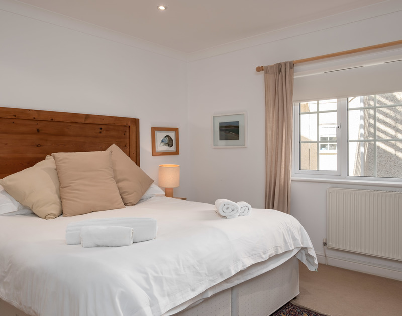 Spacious double bedroom at Bodare 1, a holiday rental at Daymer Bay, Cornwall, with kingsize bed.