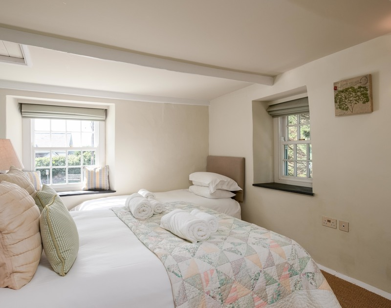 Practical family bedroom with a double and single bed, with lots of light from the two pretty sliding sash windows at self catering holiday house, Old Farm in Daymer Bay.