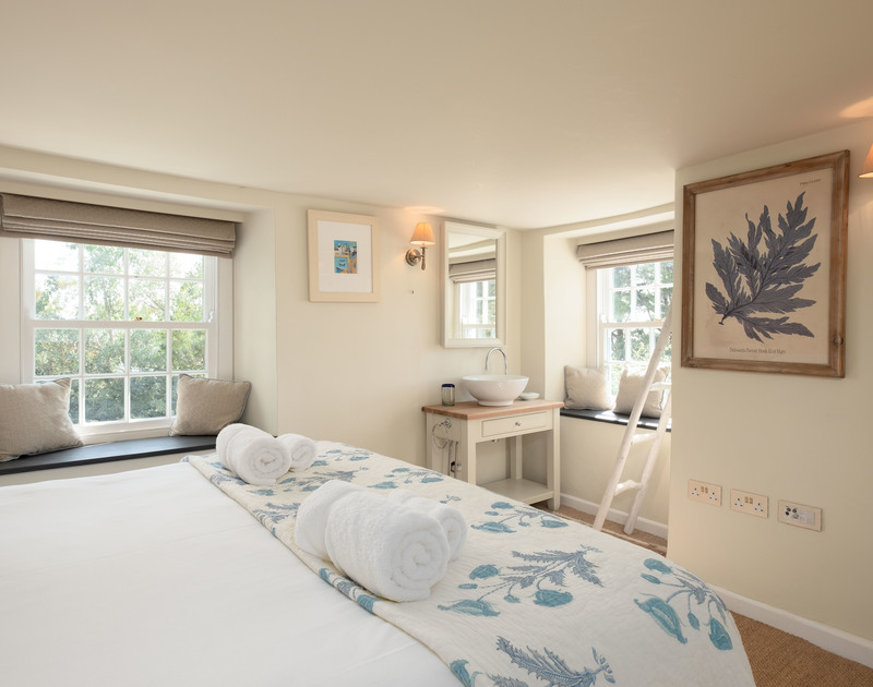 A double bedroom at Old Farm, a stunning holiday house at Daymer Bay, Cornwall, with washbasin and TV.