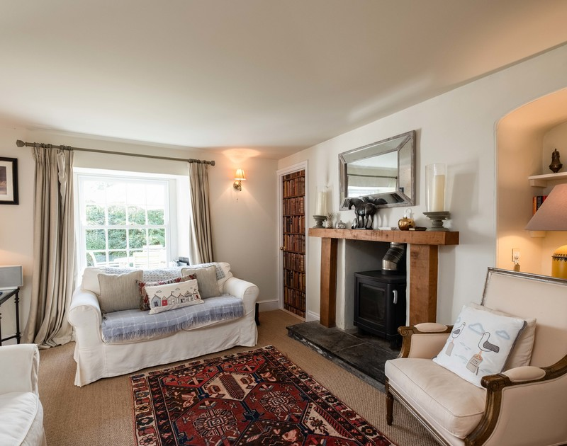 The beautifully furnished, cosy sitting room of Old Farm, a holiday house at Daymer Bay, Cornwall, with its wood burner.