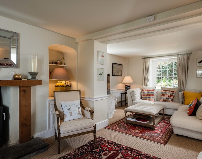 The snug TV area of Old Farm, a holiday house at Daymer Bay, Cornwall, with cosy corner sofa.