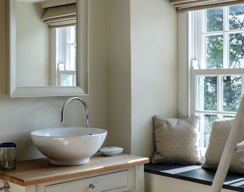 Classic hand basin and wash stand by a slate window seat in one of the gorgeous, thoughtfully furnished bedrooms at self catering Old Farm, in Daymer Bay on the North Cornish Coast.