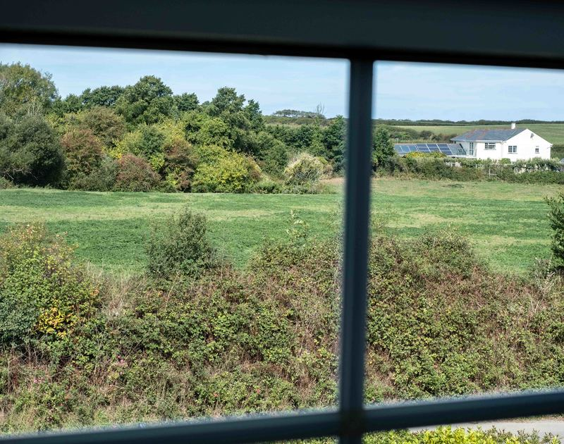 Enjoy the countrysides view from the master bedroom at Whitehay, a traditional holiday rental in Rock, Cornwall.