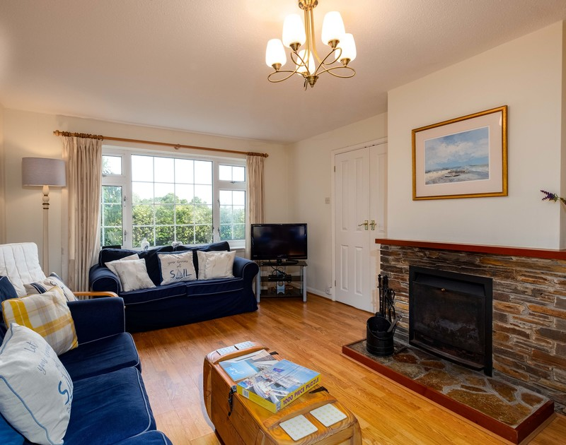 The smartly furnished sitting room of Whiteaway, a holiday house to rent in Rock, Cornwall, with its matching sofas and open fire.