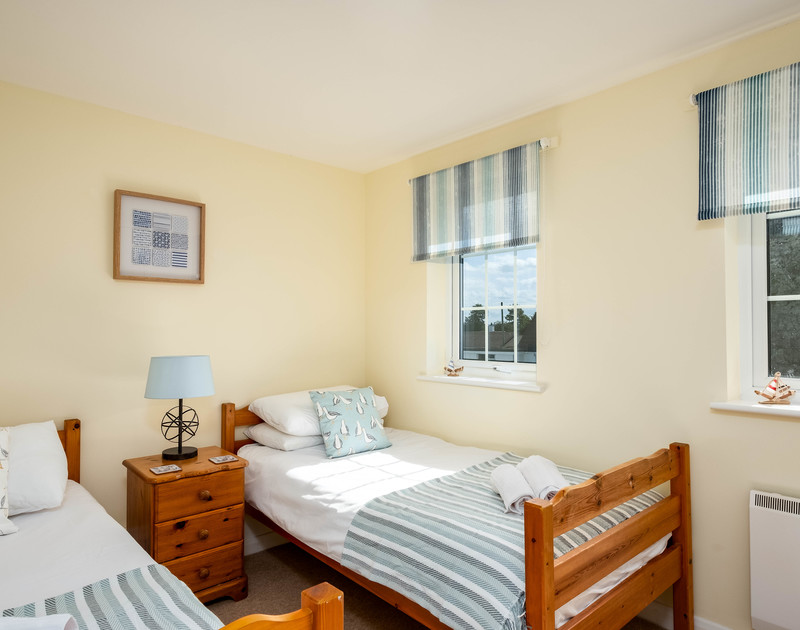 Calming coastal colours in the twin bedroom at Whitehay, a traditional holiday cottage in Rock.