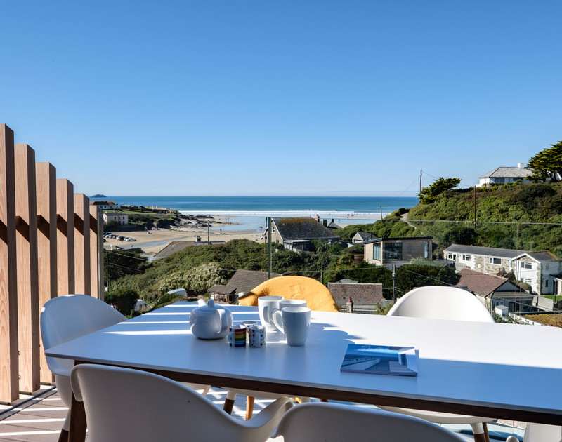 Morning coffee outside at Slatewater with views down to the beach and out to sea at Polzeath in North Cornwall.